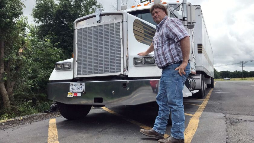 Truck driver Terry Button poses with his truck during at stop in Opal, Va., Thursday, June 13, 2019.