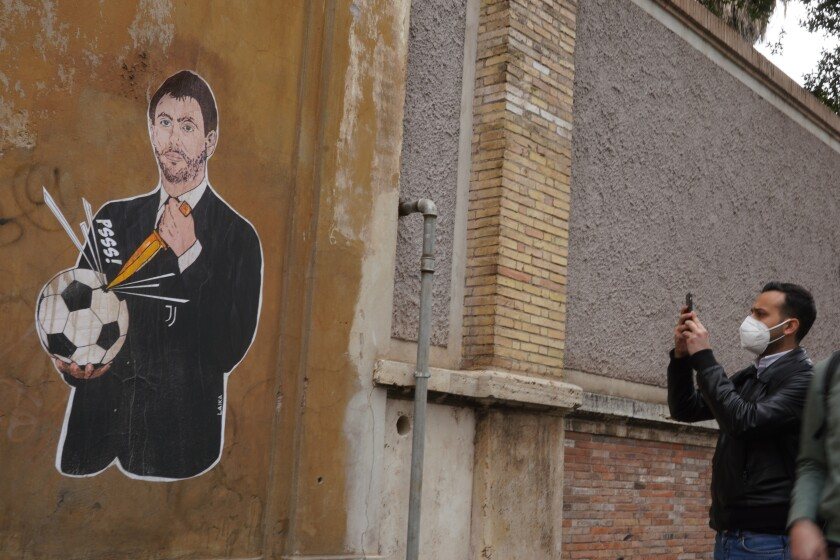 """FILE - In this Thursday, April 22, 2021 file photo, a passerby stops to take a picture of a mural depicting Juventus president Andrea Agnelli puncturing a soccer ball with a knife, in Rome. Attempting to establish a European Super League was """"not a coup"""" but rather """"a desperate cry of alarm for a system that, knowingly or not, is heading towards insolvency,"""" Juventus president Andrea Agnelli said Friday. Along with Real Madrid and Barcelona, Juventus is one of the few remaining holdouts refusing to renounce the failed Super League among the 12 founders of the project. (AP Photo/Andrew Medichini, File)"""