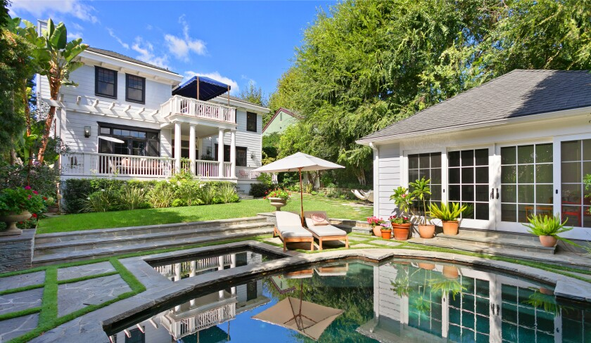 The landscaped property features a Colonial-style home built in 1922 and a newly renovated guesthouse with beamed ceilings and polished concrete floors.