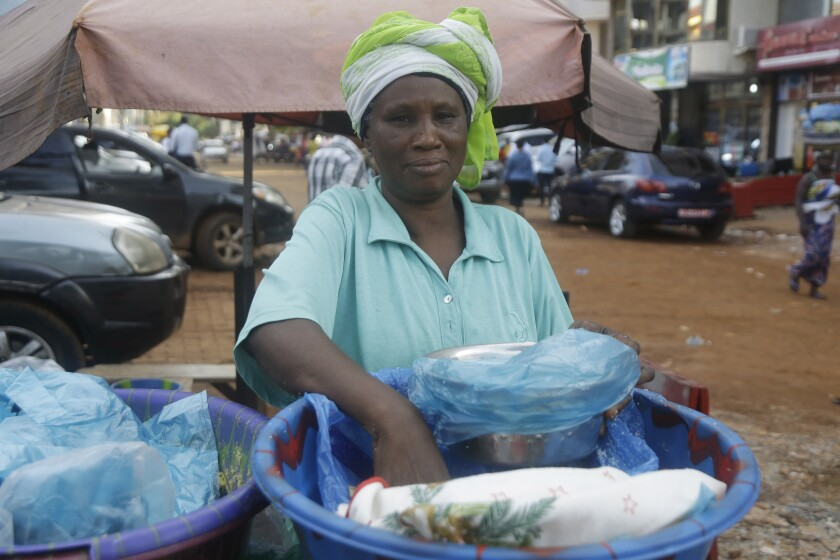 A woman sells food on a street in Conakry, Guinea, Wednesday, Sept. 8, 2021. Guinea's new military leaders sought to tighten their grip on power after overthrowing President Alpha Conde, warning local officials that refusing to appear at a meeting convened Monday would be considered an act of rebellion against the junta. (AP Photo/Sunday Alamba)