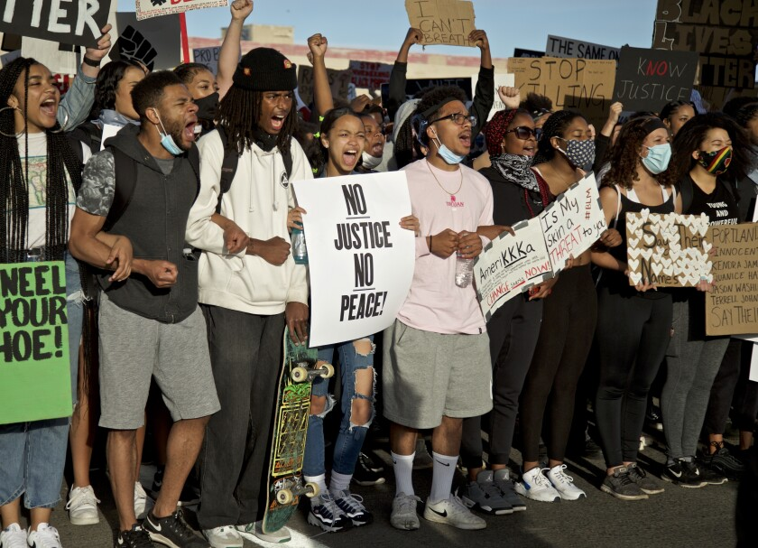 Demonstrators hold signs and shout in Portland, Ore., during a protest over the death of George Floyd, who died May 25 after being restrained by police in Minneapolis. (AP Photo/Craig Mitchelldyer)