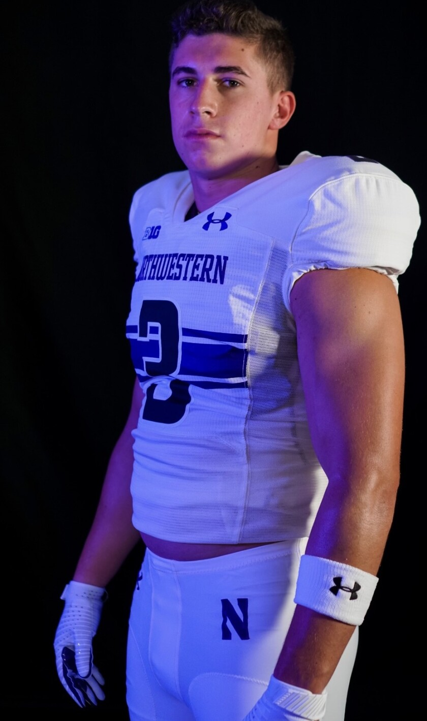 Glendora High linebacker Braydon Brus poses for a photo in a Northwestern jersey, the college to which he committed.