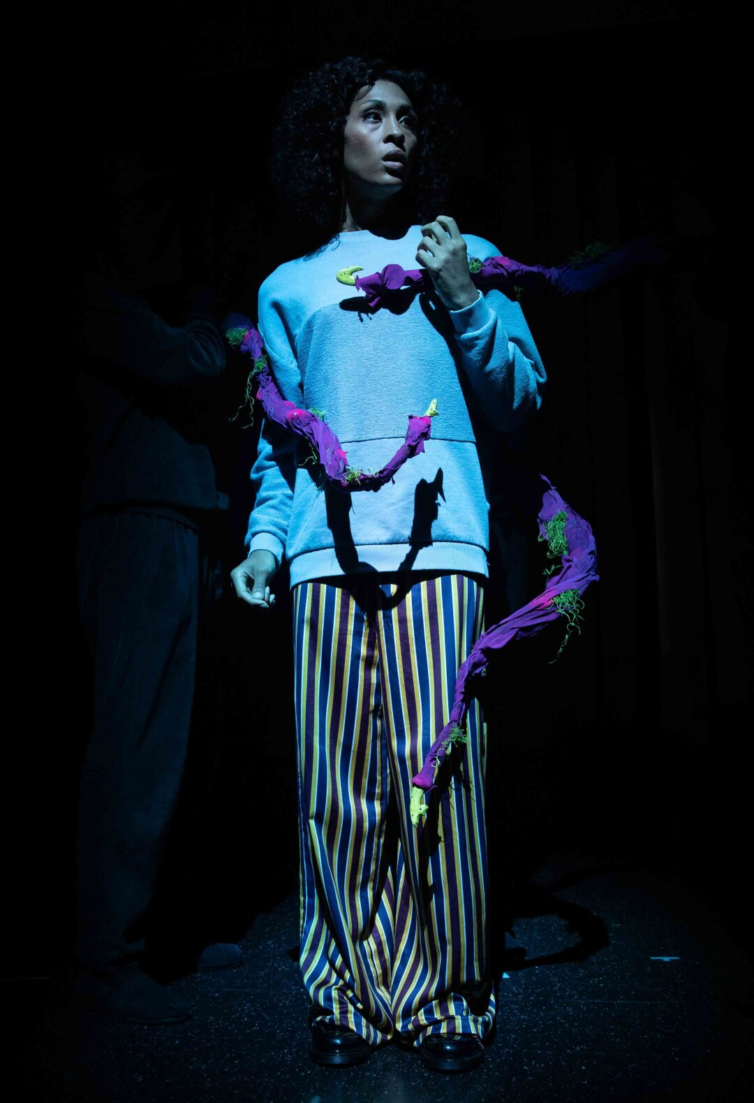 Mj Rodriguez's Audrey is taken captive by the plants tendrils, operated by puppeteers in darkness upstage.