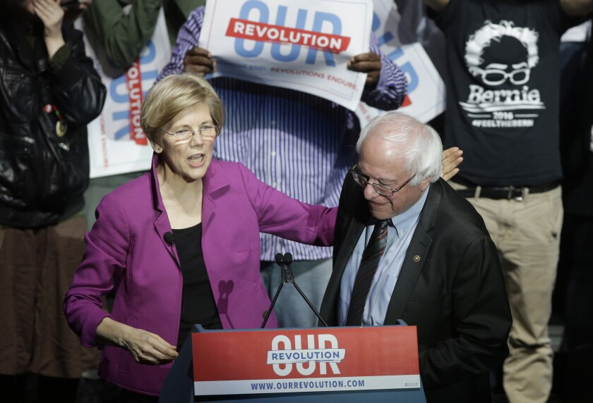 Sens. Elizabeth Warren, D-Mass., left, and Bernie Sanders, I-Vt., right, greet one another during a joint appearance at a rally Friday, March 31, 2017, in Boston.