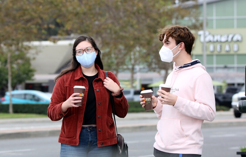 People wear masks while walking at Bristol Street and Sunflower Avenue in Costa Mesa on Nov. 6, 2020..