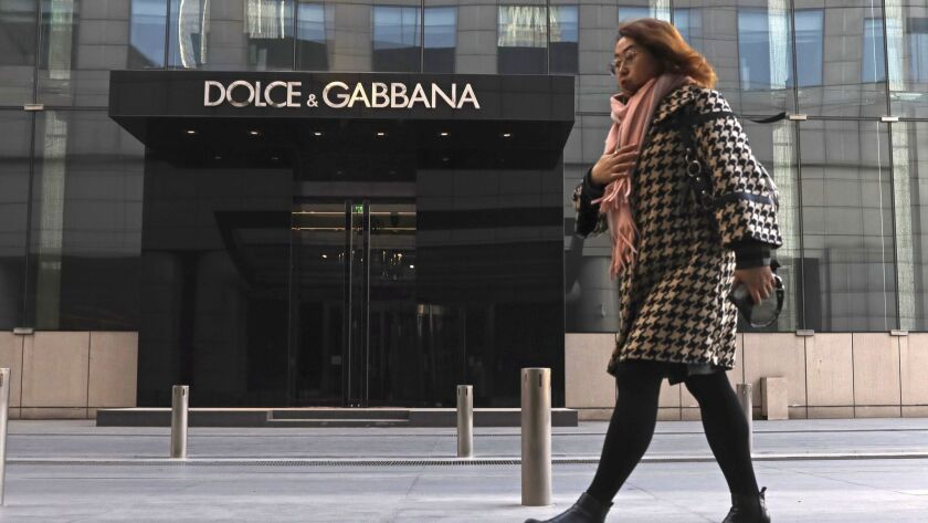 In this Nov. 25, 2018, photo, a woman walks past a Dolce&Gabbana retail outlet in Beijing, China. Do
