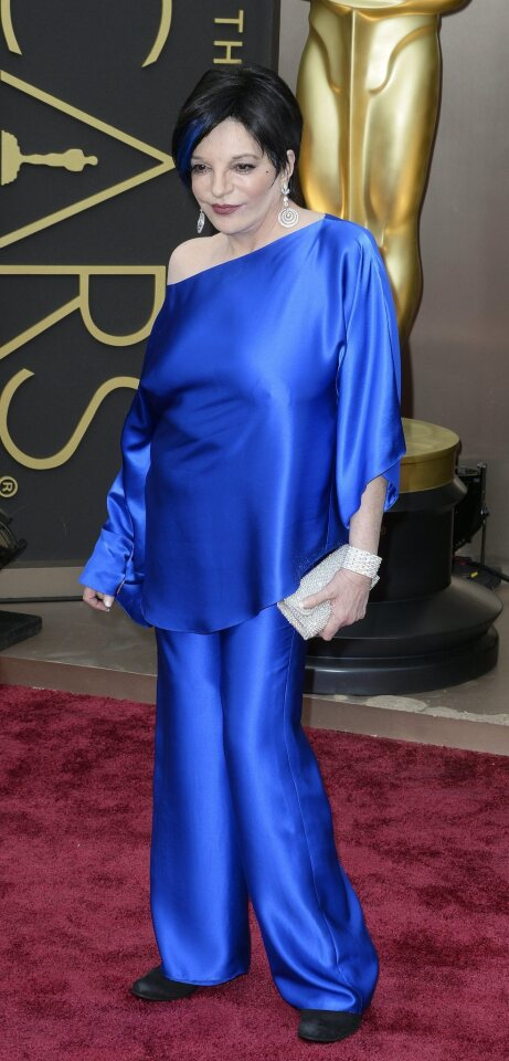 Liza Minnelli wearing vintage Halston with a blue streak in her hair to accent the diagonal line of her top, and proving you're never too old to have fun with fashion.