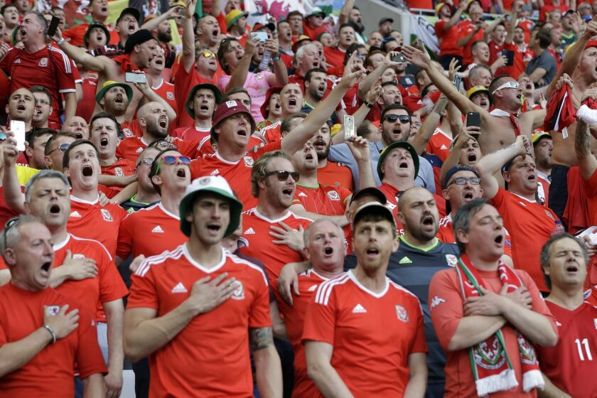 Wales' fans sing their national anthem during the Euro 2016 semifinal soccer match between Portugal and Wales, at the Grand Stade in Decines-Charpieu, near Lyon, France, Wednesday, July 6, 2016. (AP Photo/Thanassis Stavrakis)
