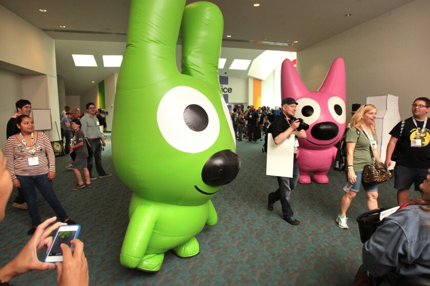 """Inflatable characters """"Yo-Yo,"""" left, and """"Hoops"""" stand in a corridor outside Comic-Con's main exhibit hall in 2013."""