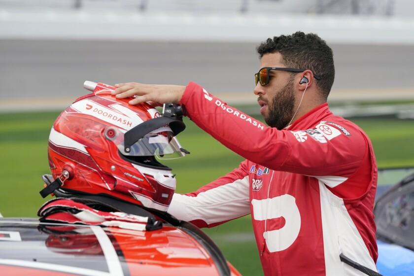 Bubba Wallace checks his helmet before the NASCAR Daytona 500 auto race at Daytona International Speedway, Sunday, Feb. 14, 2021, in Daytona Beach, Fla. (AP Photo/John Raoux)