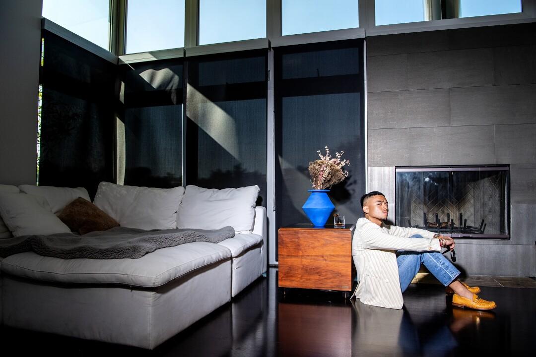 A photo of Rhuigi Villaseñor sitting on the floor near a couch.