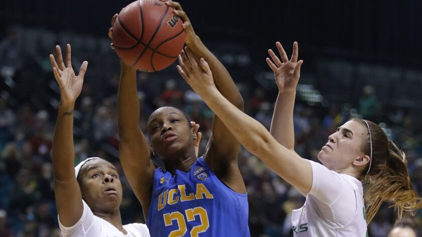 Oregon's Ruthy Hebard, left, UCLA's Kennedy Burke and Oregon's Sabrina Ionescu vie for a rebound during the first half of the semifinals of the Pac-12 women's tournament on Saturday in Las Vegas.
