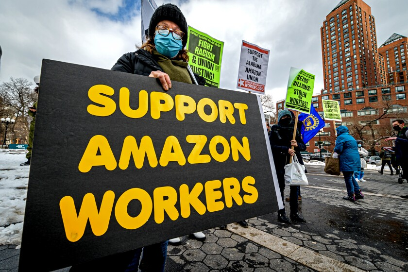 A woman in a mask alongside other labor activists holds a sign that says Support Amazon workers