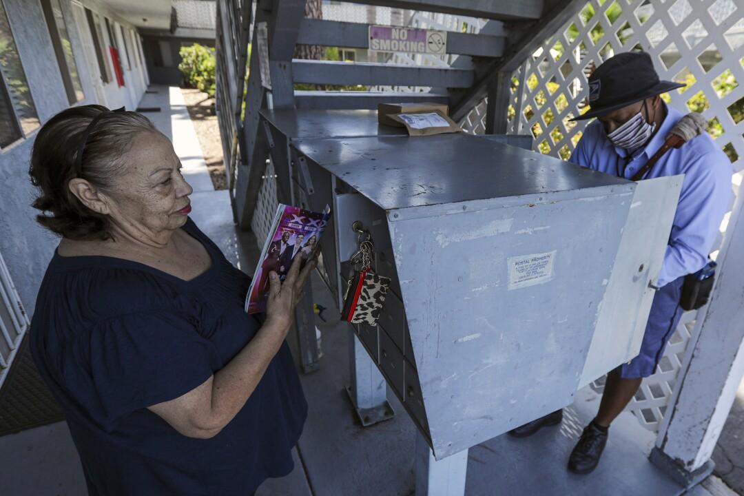 Gigi Aguilar, left, waits for checks delivered by James Daniels in San Clemente.