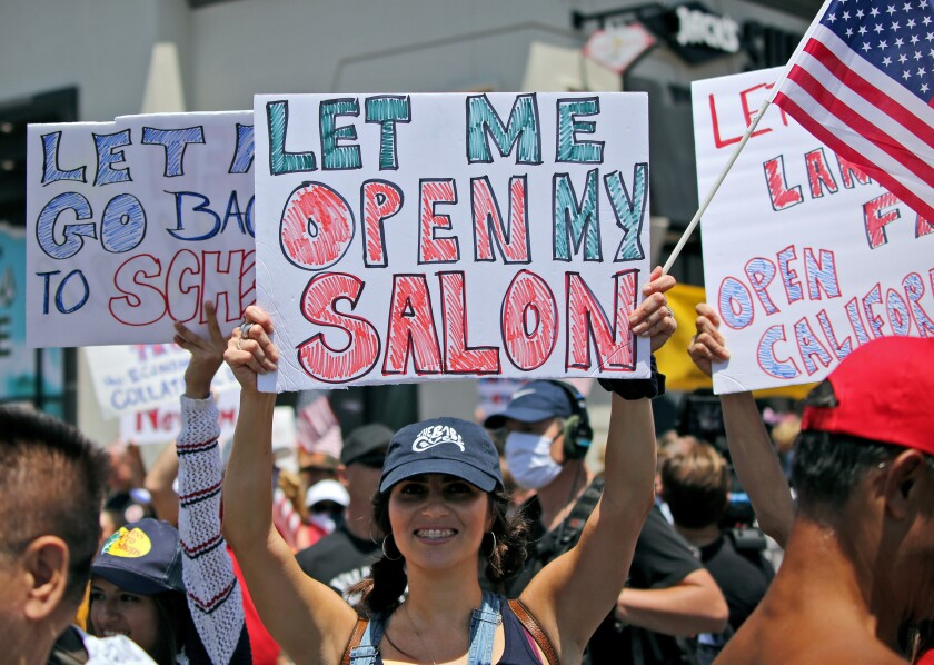 "The Babe Cave Waxing and Skincare owner Haily Lemaster, of Upland, holds a sign up during the ""Live Free Protest to Open CA."" protest at Main and Pacific Coast Highway in Huntington Beach on May 1."