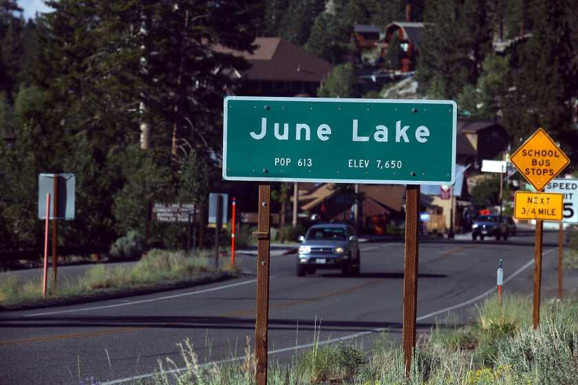 Vehicles drive through the Eastern Sierra town of June Lake. The sheriff of Mono County has a plea for the city dwellers who usually drive both its winding mountain roads and its economic engine: Stop coming.