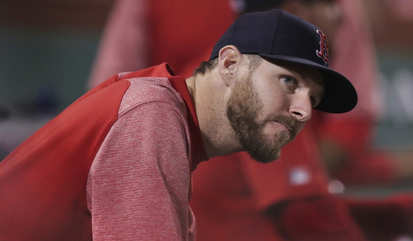 Boston Red Sox pitcher Chris Sale watches from the dugout during the fifth inning of the team's baseball game against the Philadelphia Phillies at Fenway Park in Boston, Tuesday, Aug. 20, 2019.