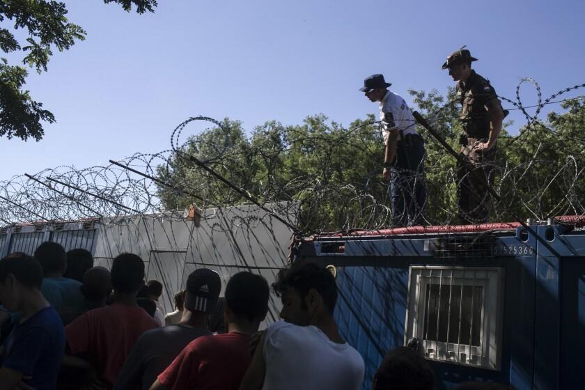 Policías y militares húngaros supervisan el reparto de comida mientras la gente hace fila en un campo migrante en la frontera serbia con Hungría, en Horgos, Serbia, el lunes 11 de julio de 2016. (AP Foto/Marko Drobnjakovic)