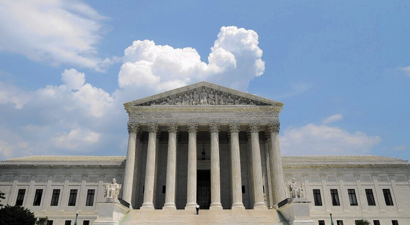 The U.S. Supreme Court building against a blue sky and clouds.