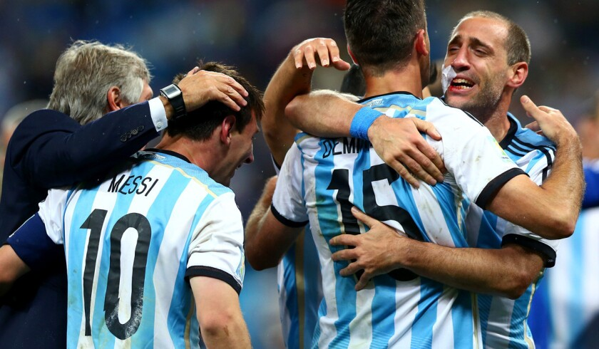Argentina teammates Lionel Messi (10), Martin Demichelis (15) and Pablo Zabaleta celebrate after defeating the Netherlands on penalty kicks, 4-2, in a World Cup semifinal on Wednesday at Arena Corinthians in Sao Paulo, Brazil.