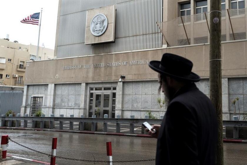 Un judío ultraortodoxo revisa su móvil mientras pasa delante de la Embajada de Estados Unidos en Tel Aviv (Israel) hoy, 6 de diciembre de 2017. EFE