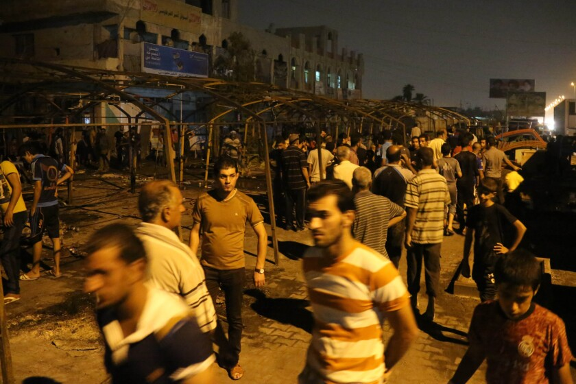 Passersby check out the site of a double suicide bomb attack at a funeral in the Shiite Muslim neighborhood of Sadr City in Baghdad. At least 72 people were killed and more than 120 wounded, police said.