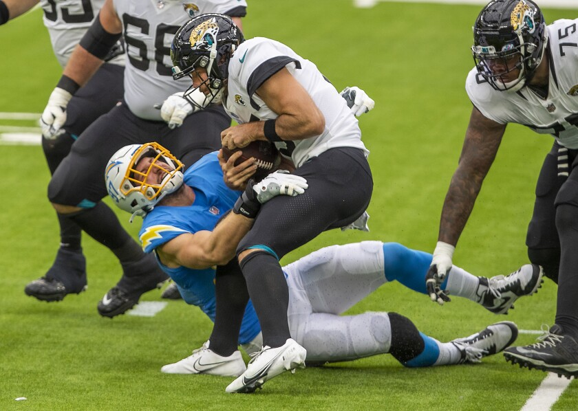 Chargers defensive end Joey Bosa assists in sacking Jaguars quarterback Gardner Minshew at SoFi Stadium.