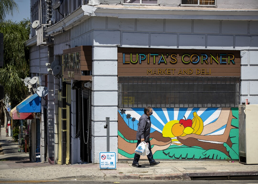 A man carries a bag of food past a mural at Lupita's Corner Market And Deli