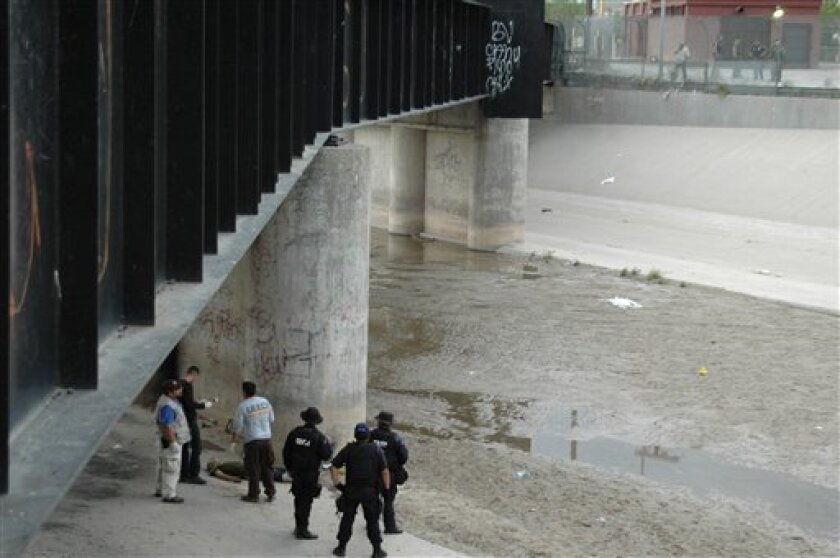 Mexican federal police and forensic experts stand next to the body of 14 year-old Sergio Adrian Hernandez Huereca, under the Paso Del Norte border bridge, as US officials watch from the US side at right, in Ciudad Juarez, northern Mexico, Monday, June 7, 2010. Chihuahua state officials released a statement Tuesday, June 8, demanding a full investigation into the death of the boy who was allegedly shot by a U.S. Border Patrol agent after a confrontation, according to Mexican authorities.(AP Photo)