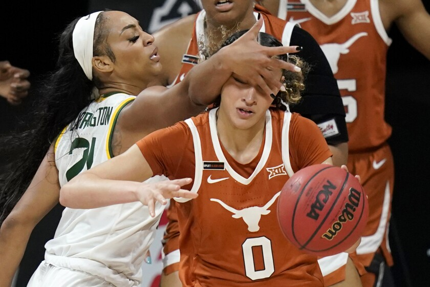 Texas guard Celeste Taylor (0) is fouled by Baylor guard DiJonai Carrington (21) during the second half of an NCAA college basketball game in the semifinal round of the Big 12 Conference tournament in Kansas City, Mo., Saturday, March 13, 2021. (AP Photo/Orlin Wagner)