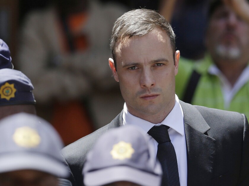 Oscar Pistorius is escorted by police officers as he leaves the high court in Pretoria, South Africa, on Oct. 17.