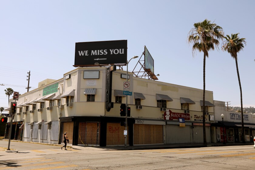 "A billboard above Bobby Kim's the Hundreds store, which is now boarded up, states, ""We Miss You."""