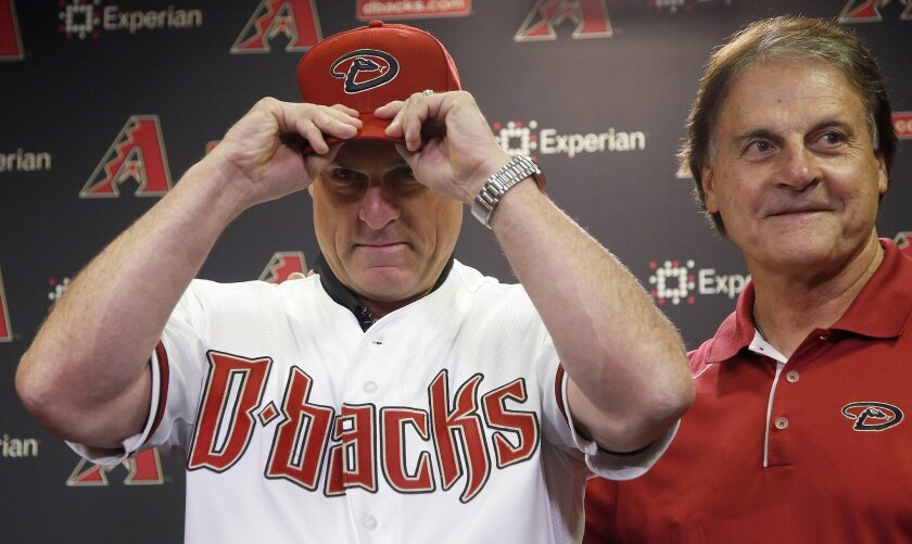 FILE - In this Oct. 13, 2014, file photo, new Arizona Diamondbacks baseball team manager Chip Hale, left, puts on a Diamondbacks hat as he is introduced by chief baseball officer Tony LaRussa at a news conference in Phoenix. As position players report to spring training for the Diamondbacks, competition looms for a spot in the opening day lineup under new manager Chip Hale. (AP Photo/Ross D. Franklin, File)