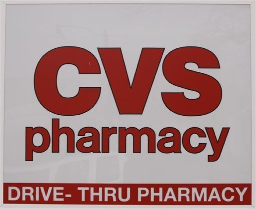 A CVS pharmacy sign is displayed outside a store in Foxborough, Mass., Feb. 7, 2012. CVS Caremark said Wednesday, Feb. 8, 2012, its fourth-quarter earnings climbed nearly 4 percent, as the drugstore operator's pharmacy services revenue swelled due to a long-term contract and new business. (AP Photo/Stephan Savoia)