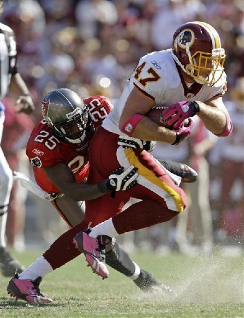 Washington Redskins tight end Chris Cooley is stopped by Tampa Bay Buccaneers cornerback Aqib Talib during the second half of the NFL football game in Landover, Md., Sunday, Oct. 4, 2009. (AP Photo/Alex Brandon)