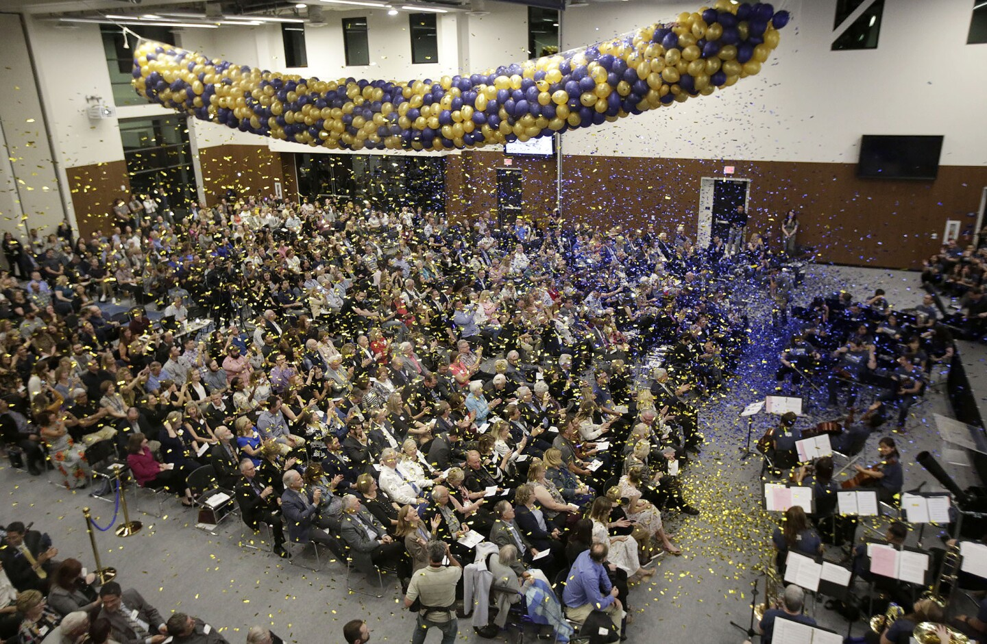 Over a thousand guests watch as confetti flies during 100 year anniversary and new Fred and Ruth Waugh Student Center unveiling ceremony at Vanguard University on Friday.