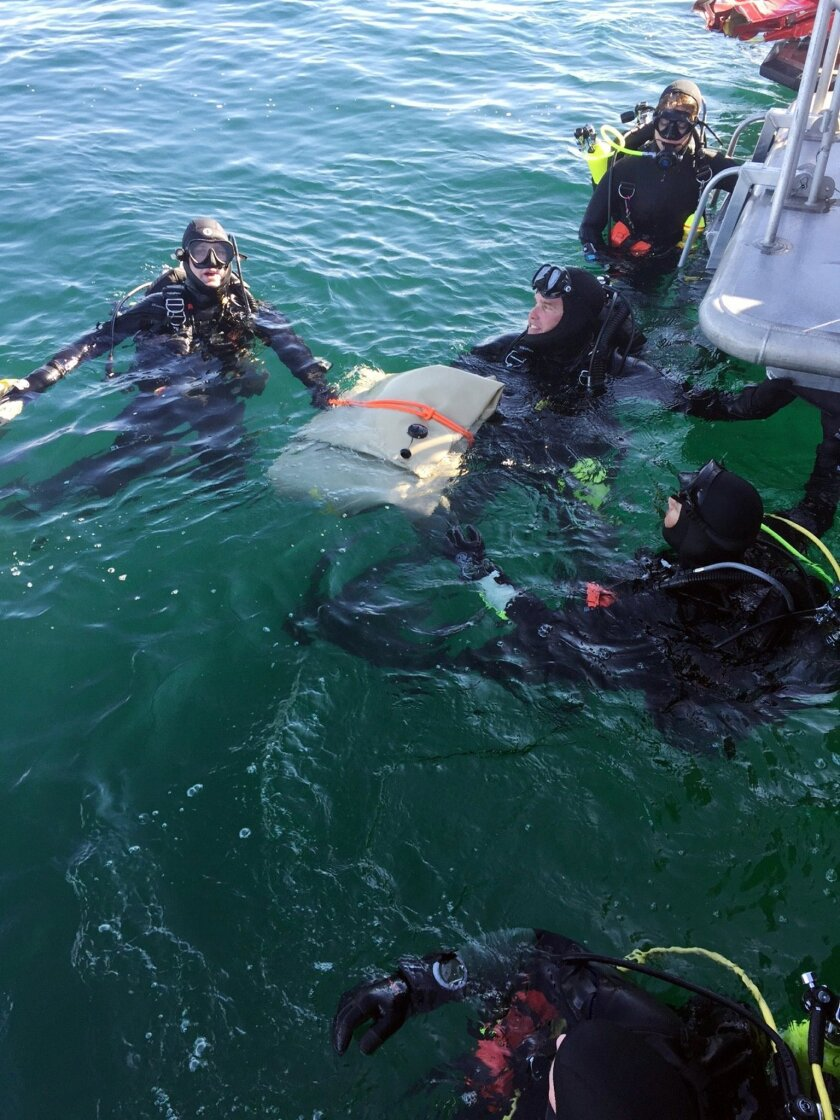 In this Sunday, Feb. 7, 2016 photo provided by the Los Angeles County Sheriff's Department, divers with the department's Special Enforcement Bureau surface with wreckage from one of two small planes that collided in midair and crashed into the ocean Friday off the coast near Los Angeles. Two bodies