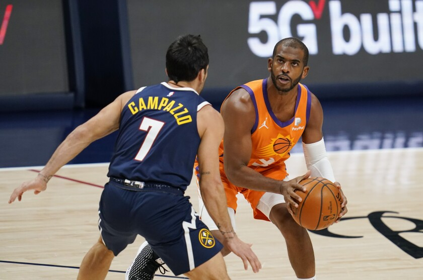 Phoenix Suns guard Chris Paul, right, looks for a shot over Denver Nuggets guard Facundo Campazzo during the first half of an NBA basketball game Friday, Jan. 1, 2021, in Denver. (AP Photo/David Zalubowski)
