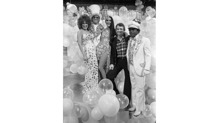 "January 1975: Four luminaries wearing designs by Bob Mackie take a break with the designer during taping of ""The Cher Show."" From left: Bette Midler, Elton John, Cher, Bob Mackie and Flip Wilson."