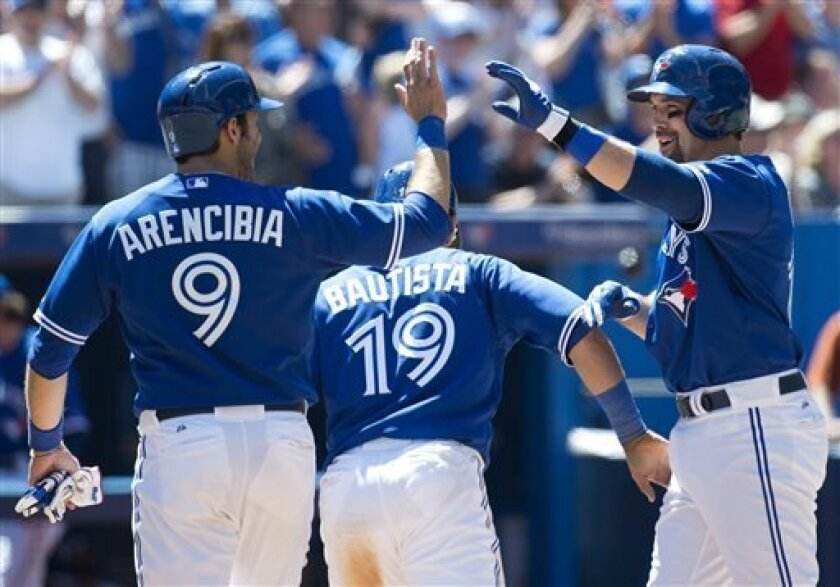 Toronto Blue Jays third baseman Mark DeRosa, right, celebrates his three-run home run with teammates J.P. Arencibia, left, and Jose Bautista while playing against the Seattle Mariners during fifth inning MLB American League baseball action in Toronto on Sunday, May 5, 2013. (AP Photo/THE CANADIAN PRESS,Nathan Denette)