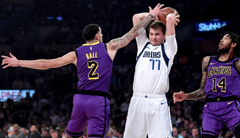 Lakers guard Lonzo Ball pressures Mavericks guard Luka Doncic during the game Friday night at Staples Center.