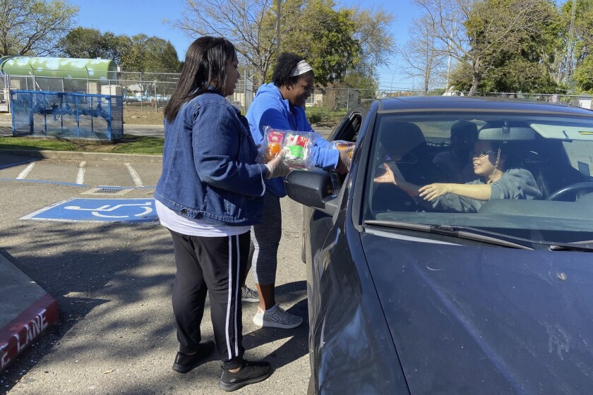 In this Tuesday, March 10, 2020, photo, Florin Elementary School staff hand out food to students and parents driving in, after their facility closed in response to the coronavirus Sacramento, Calif. (AP Photo/Cuneyt Dil)