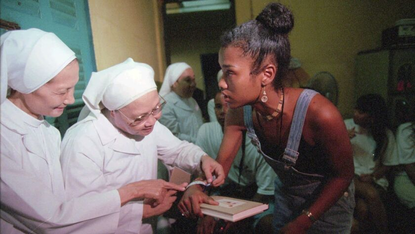 A woman shows her ID bracelet with her former name and orphanage location to Catholic nuns at an orphanage in Ho Chi Minh City on June 21, 1996. She was one of 12 orphans evacuated during the last days of the Vietnam War who returned for a tour of their homeland.