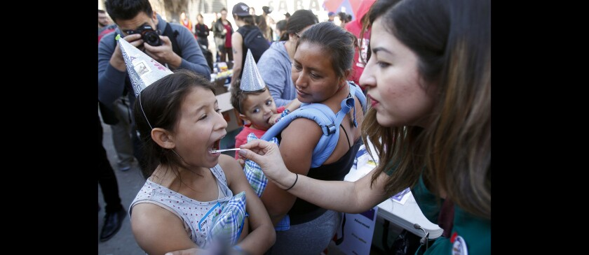 Roxette Villegas, a registered nurse for Los Angeles County, checks the temperature of Amy Gisell Escobar Mejia, 7, as Amy's mother Patricia del Carmen Escobar, from El Salvador, watches as she holds her her son Carlos Ulises Martinez Escobar, 3, while outside of the El Barretal shelter in Tijuana.