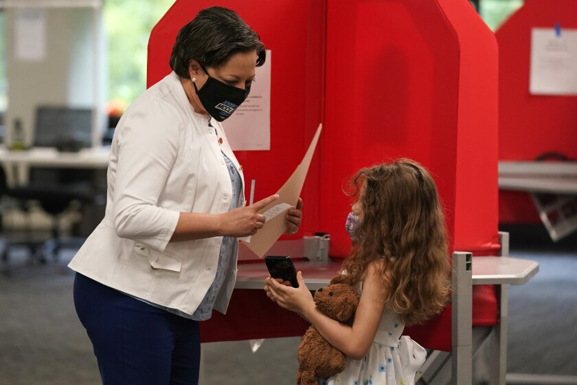 Democratic gubernatorial candidate, Virginia State Sen. Jennifer McClellan, left, shows her daughter Samantha, right, her ballot at an early voting location in Richmond, Va., Saturday, May 29, 2021. McClellan faces four other Democrats in the primary. (AP Photo/Steve Helber)