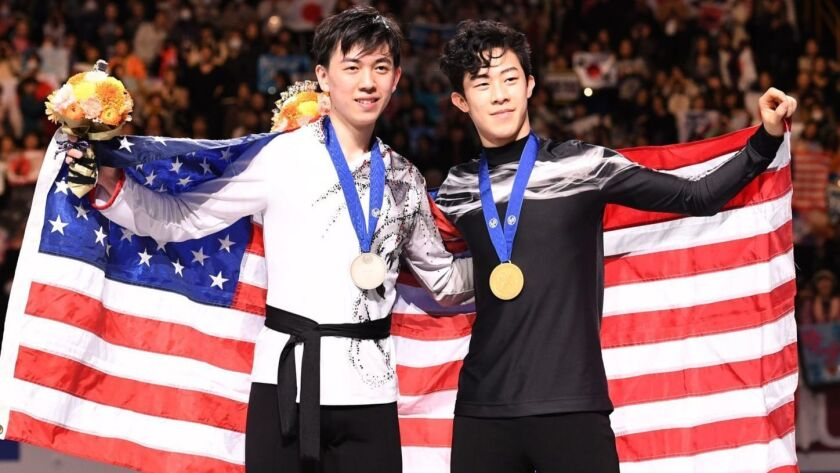 Gold medalist Nathan Chen, right, and bronze medalist Vincent Zhou pose for a photo after the figure skating world championships on Saturday.