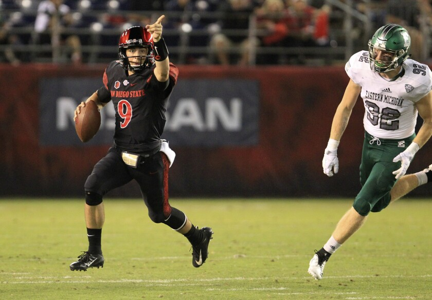 Aztecs quarterback Ryan Agnew signals to his receiver as he pursued by Eastern Michigan's Maxx Cros