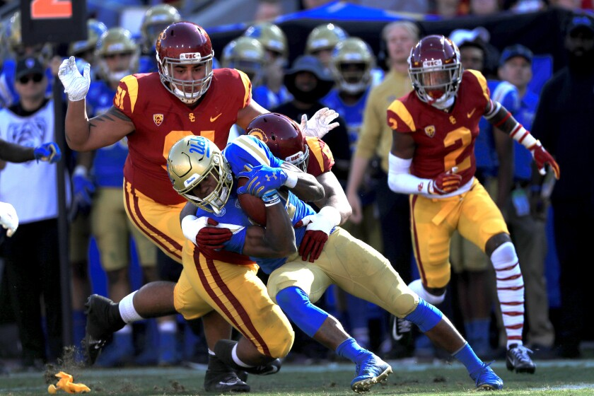 UCLA running back Joshua Kelley, center, is tackled by USC's Marlon Tuipulotu.