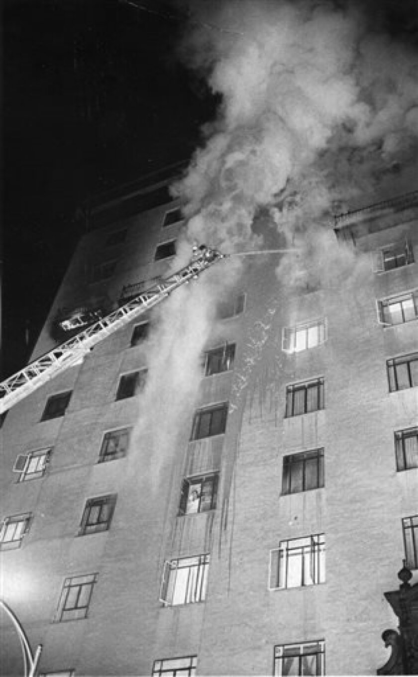 FILE - In a Dec. 20, 1970 file photo Tucson, Ariz., firefighters apply a steady stream of water during the Pioneer International Hotel fire , that resulted in 29 deaths.      Louis Cuen Taylor who has spent more than four decades in prison for the hotel fire is expected to be released Tuesday, Apri