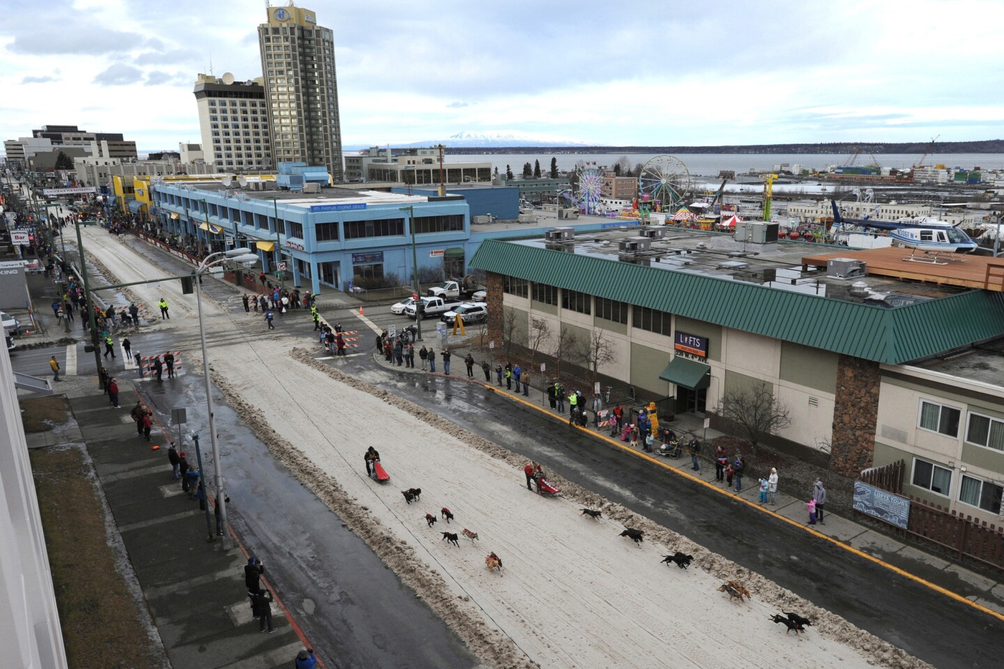 Alaska had the second-warmest December through February of the last century, and many parts of the state, including Anchorage, are seeing their warmest winters ever. Mushers drive their dog teams down a ribbon of snow that was placed in a snowless downtown Anchorage.